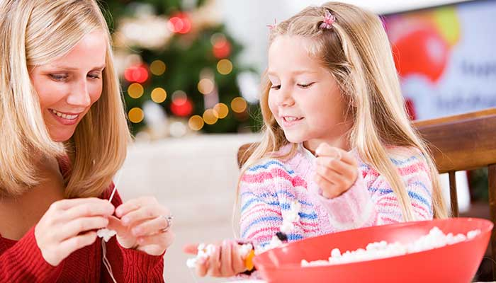 mother and daughter stringing popcorn garland