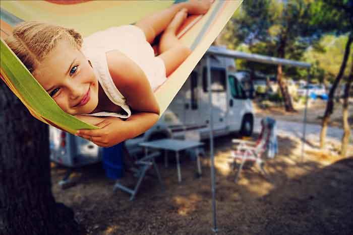 child in hammock rv in background