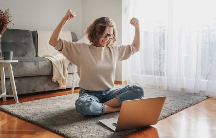 woman celebrating in front of her computer