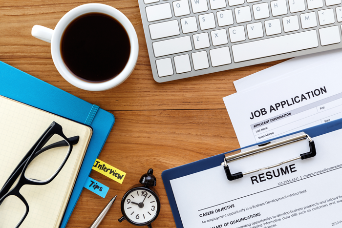 job application and resume sitting on a desk next to a computer